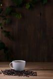 Taza de café y granos de café en de madera Fotos de archivo