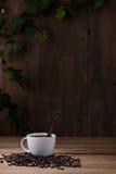 Taza de café y granos de café en de madera Fotografía de archivo