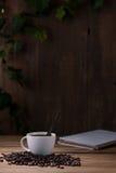 Taza de café y granos de café en de madera Fotos de archivo libres de regalías