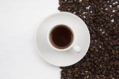 Taza de café y granos de café en el fondo blanco Fotografía de archivo