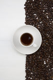 Taza de café y granos de café en el fondo blanco Imagen de archivo libre de regalías