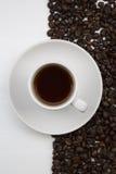 Taza de café y granos de café en el fondo blanco Imagen de archivo