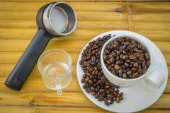 Taza de café y granos de café en el fondo de bambú Imagen de archivo