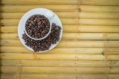 Taza de café y granos de café en el fondo de bambú Foto de archivo
