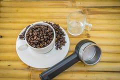 Taza de café y granos de café en el fondo de bambú Fotografía de archivo libre de regalías