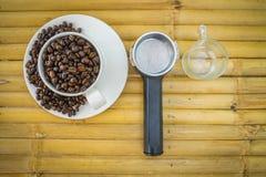 Taza de café y granos de café en el fondo de bambú Fotos de archivo