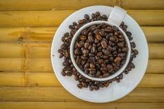 Taza de café y granos de café en el fondo de bambú Fotos de archivo libres de regalías