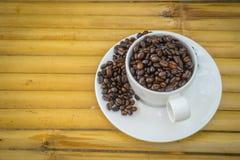Taza de café y granos de café en el fondo de bambú Imagenes de archivo
