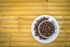 Taza de café y granos de café en el fondo de bambú Foto de archivo libre de regalías