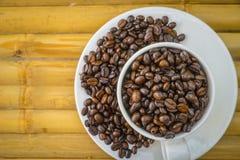 Taza de café y granos de café en el fondo de bambú Imagen de archivo libre de regalías