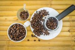 Taza de café y granos de café en el fondo de bambú Imágenes de archivo libres de regalías
