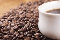 Taza de café y granos de café en la tabla Imagen de archivo
