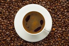 Taza de café y granos de café en la tabla Fotografía de archivo libre de regalías