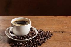 Taza de café y granos de café en la tabla Fotos de archivo libres de regalías