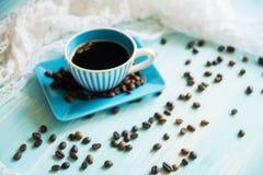 Taza de café y granos de café en la tabla Fotos de archivo
