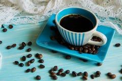Taza de café y granos de café en la tabla Imágenes de archivo libres de regalías