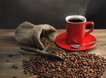 Taza de café y granos de café en la tabla de madera Foto de archivo libre de regalías