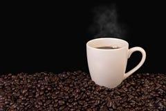 Taza de café y granos de café en negro Imagen de archivo