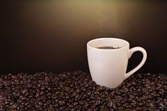 Taza de café y granos de café en negro Imágenes de archivo libres de regalías