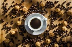 Taza de café y granos dispersados del café en la tabla y las galletas Fotos de archivo
