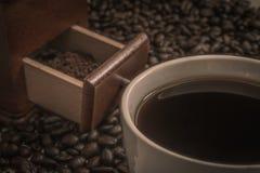 Taza de café y granos de café en la tabla con el polvo en amoladora de café Fotos de archivo