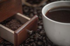 Taza de café y granos de café en la tabla con el polvo en amoladora de café Fotografía de archivo libre de regalías