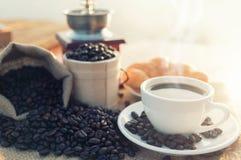 Taza de café y granos de café en la tabla de madera Fotos de archivo