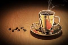 Taza de café y granos de café en una tabla de madera foto de archivo
