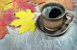 Taza de café y de hojas de arce amarillas en una tabla de madera fotografía de archivo libre de regalías