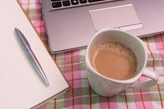 Taza de café y ordenador portátil y nota sobre el paño Foto de archivo libre de regalías