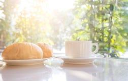 Taza de café y de pan en la tabla Imagenes de archivo