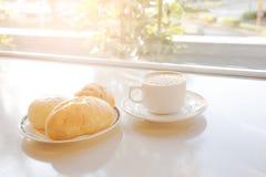 Taza de café y de pan en la tabla Imagen de archivo