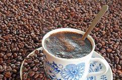 Taza de café y pila de granos de café Foto de archivo