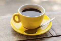 Taza de café y platillo amarillos saltados en una tabla de madera, primer con una profundidad del campo baja imagen de archivo