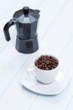 Taza de café y pote del moka con los granos de café en la tabla Imagen de archivo libre de regalías