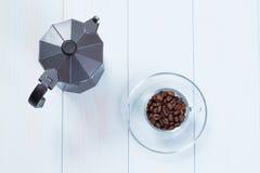 Taza de café y pote del moka con los granos de café en la tabla Fotos de archivo libres de regalías