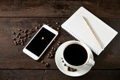 taza de café y de smartphone en la madera Fotografía de archivo