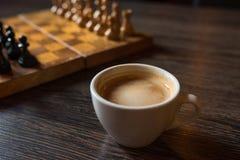 Taza de café y de tablero de ajedrez en una perspectiva en una tabla de madera foto de archivo libre de regalías