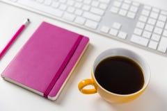 Taza de café y teclado de ordenador en el escritorio Imágenes de archivo libres de regalías