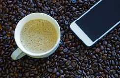 Taza de café y teléfono elegante con los granos de café Imagen de archivo libre de regalías
