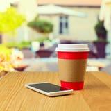 Taza de café y teléfono móvil en cafetería imagenes de archivo
