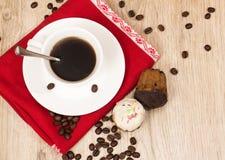 Taza de café y un puñado de biscotti hecho en casa con el chocolate y las almendras en una tabla de madera Imagen de archivo