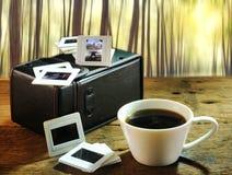 Taza de café y viejas diapositivas de película de las memorias del arte y de la cultura encendido Imagen de archivo libre de regalías