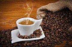 Taza de café caliente con las habas Fotos de archivo libres de regalías