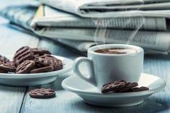 Taza de café, de galletas del chocolate y del periódico del fondo Humo que sube de la taza Imagen de archivo libre de regalías