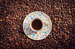 Taza de café de la mañana con el platillo en el fondo con las habas, visión superior Fotografía de archivo libre de regalías