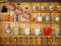 Taza de café en el estante de madera Fotos de archivo