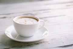 Taza de café en la tabla blanca Fotografía de archivo