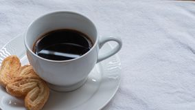 Taza de caf? griego o turco, en la peque?a placa blanca del platillo, con dos pasteles de la galleta, en la superficie blanca del imagen de archivo libre de regalías