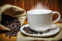 Taza de café y de granos de café con humo en de madera viejo Imagen de archivo